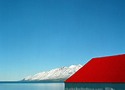 A red roofed farm building overlooking Fjord Eyjafjordur and snowy mountains, near Dalvik, Iceland