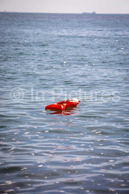 An orange life jacket that was used by an asylum seeker floating in the sea on the 8th of October 2021 in Folkestone, United Kingdom. The jacket fell from a dinghy as the coast guards pulled it to shore. The boat brought 13 Asylum seekers safely to the beach who then removed their jackets once they arrived.