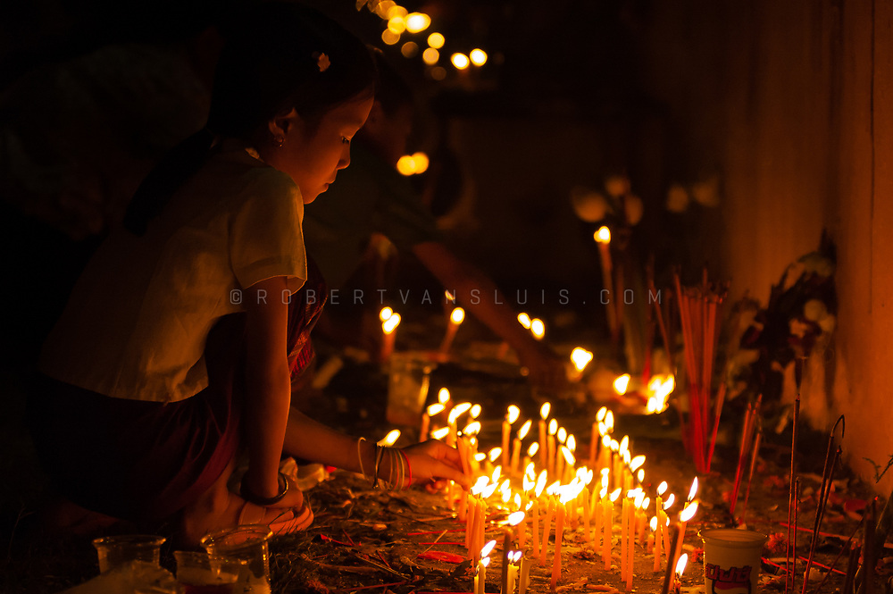 A girl lights candles during the evening ceremony at the That Luang Festival in Vientiane, Laos. Photo ©robertvansluis.com