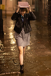 © Licensed to London News Pictures. 20/10/2021. London, UK. A woman attempts to use a book to shelter from heavy rain as she walks during heavy rain in Greenwich South East London. An Amber weather warning for rain is in place for parts of London and South East England.  Photo credit: George Cracknell Wright/LNP