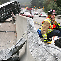 Scotts Valley firefighters wait for an ambulance to arrive as they stabilize the driver of a red Nissan Maxima who reportedly bumped the overturned delivery truck at top, sending oth cars careening out of control on Highway 17 in Scotts Valley, California.<br /> Photo by Shmuel Thaler <br /> shmuel_thaler@yahoo.com www.shmuelthaler.com