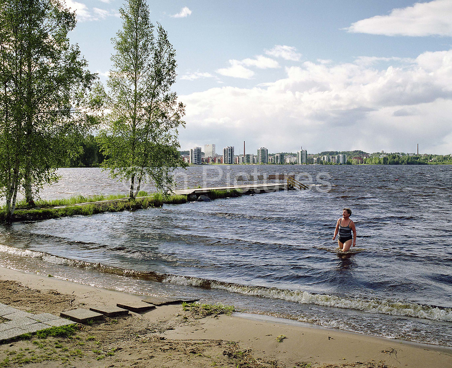 After taking a sauna, a woman returns from a swim in Lake Jyvasjarvi, Jyvaskyla, Central Finland. Jyvaskyla is the capital of Central Finland and the largest city in the Finnish Lakeland, an area of more than 188,000 lakes. During the summer months taking a sauna followed by swimming in the lake around the city is a popular activity.