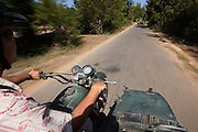 Man on motorcycle and sidecar drives through the landscapes of Siem Reap Province in Cambodia