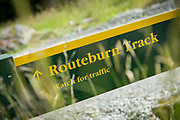 Close-up shot of a hiking trail post with yellow letters on a green background, Routeburn Shelter, South Island, New Zealand