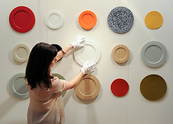 """© under license to London News Pictures. LONDON, UK  05/05/2011. A gallery worker positions a plate featured in Sabastian Bergne and Sophie Smallhorn's """"Colourware"""". The unveiling today (5 May 2011) of Tracey Emin's first tapestry ahead of the launch of COLLECT, the Crafts Council's international craft fair for contemporary objects at the Saatchi Gallery, London. Photo credit should read Stephen Simpson/LNP."""