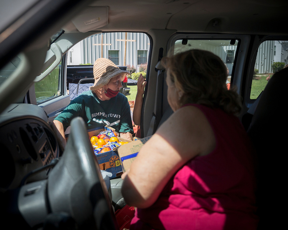 SUMMERTOWN, GA - JULY 14, 2020: Volunteers with the Summertown Food Pantry take part in a mobile food drive at the Summertown Baptist Church. Food insecurity was already worse in rural Georgia before the pandemic began. The virus has only exacerbated those disparities and increased concerns that families are now facing hunger. (AJC Photo/Stephen B. Morton)