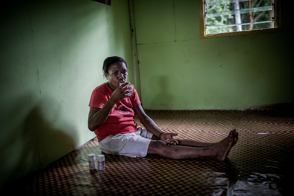 """Mama Yuli takes her ARV pills at eight o'clock every morning for the last eight years.<br /> <br /> In 2004 Mama Yuli contracted the HIV virus from her husband who later died from AIDS. At her worst point, Mama Yuli was just skin and bones weighing only 22 kilograms (48 pounds). With ARV she is now healthy to work and support her family.<br /> <br /> If taken properly and regularly, ARV has been proven to prolong the survival rate of people living with HIV/AIDS and enables them to live a productive life. The Indonesian government started providing ARV therapies in 2003. In that year only 7 packages of ARV were purchased for all of Papua. Each package cost approximately $5000. Today in Indonesia this vital medication can be obtained at no cost only in Papua but only 12% of those with HIV/AIDS are undergoing ARV therapy.<br /> <br /> Despite these advances, ARV is mostly available only in cities. Collaboration between health facilities in urban centers and staffs in rural areas to make ARV more accessible for patients living in the countryside is still lacking as well as the endorsement of ARV as a legitimate medicine for HIV/AIDS. Sometimes health staff and even educational materials still provide misleading information and perception such as """"there is no medicine for HIV/AIDS.""""<br /> <br /> As a general practice health personnel often evaluate patients for their adherence in taking their medication and keeping up with appointments before allowing them to undergo ARV therapy. Indigenous Papuans tend to fall short of this assessment and fail to return for their check-up because many of them live too far from the health centers.  At times, they do not fully understand the benefits of ARV medication and the importance of taking them properly due to poor counseling from the health staff.  Also, many of them are unable to keep their appointments or take medication regularly because they still keep their status a secret from their immediate family members or spouse."""