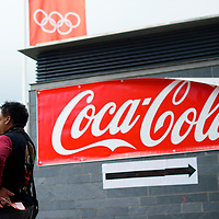 An attendee imbibes a Coca Cola, a principal sponsor of the Olympiad, outside the ExCel Exhibition Centre during the 2012 London Summer Olympics.