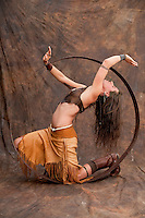 Studio photograph of a western tribal style woman wearing leather fringe dress and snakebone belt while moving in a large hoop.