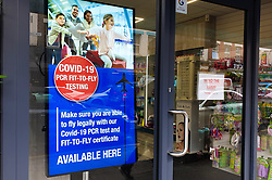 © Licensed to London News Pictures. 09/08/2021. London, UK. PCR advert displayed on a pharmacy's window in north London. Health Secretary Sajid Javid has asked the UK's competition watchdog to investigate PCR Covid test firms that are selling tests at excessive prices and engaging in exploitative practices following complains from holidaymakers of high prices and poor service from many of the 400-plus firms offering PCR tests. Photo credit: Dinendra Haria/LNP