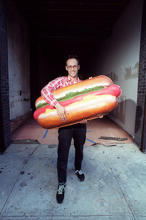 Photographs of Brian Benavidez at his soon-to-be hot dog stand/restaurant called Sparky's in Williamsburg. He is seen with a large hot dog which will adorn the finished store. JUSTIN LANE FOR THE NEW YORK TIMES ORG XMIT: 200207715