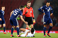 Omri Ben Harush (20) (Lokeren)of Israel gets a helping hand from Scotland midfielder Graeme Shinnie (15) (Aberdeen) but gets no sympathy from Referee Tobias Welz during the UEFA Nations League match between Scotland and Israel at Hampden Park, Glasgow, United Kingdom on 20 November 2018.