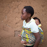 A young girl carries a baby in Butembo, Congo. Her family is involved in helping build a well with support from IMA and Tearfund. Clean drinking water underpins many initiatives for healthcare in  the region.