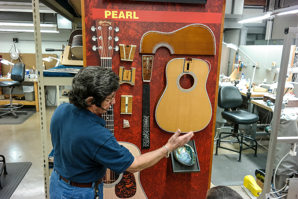 Nazareth, PA, USA - October 27, 2014:  The factory tour guide at C.F. Martin & Co. Factory in Nazareth, Pennsylvania, explaining guitar components.