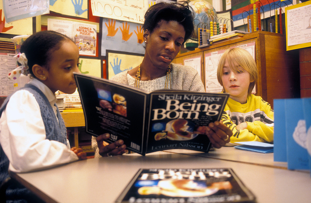 Teacher reading to pupils about human biology and childbirth,