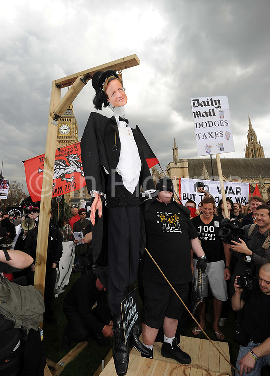 An effigy  of Leader of the Conservative Party, David Cameron is placed in fake gallows and hung during a mock execution held in Parliament Square during a May Day demonstration, London.
