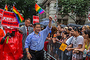 New York City comptroller John Liu, in the blue shirt., waves a rainbow flag as he marches down Christopher Street.