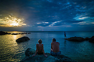 A couple sit on a rock of Long Beach at sunset, Phu Quoc Island, Kien Giang Province, Vietnam, Southeast Asia