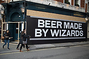 Beer made by wizards hoarding on a building under redevelopment in London, England, United Kingdom.