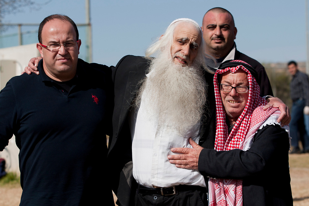 Rabbi Menachem Froman (C), is escorted by an unidentified shiekh and by another man after feeling sick during a friendly soccer match between Israelis and Palestinians held at the Jewish settlement of Efrat in Gush Etzion, on January 28, 2010. Rabbi Froman, an Orthodox rabbi and a peacemaker and negotiator with close ties to Palestinian religious leaders from the PLO and Hamas, suffers from colorectal cancer.