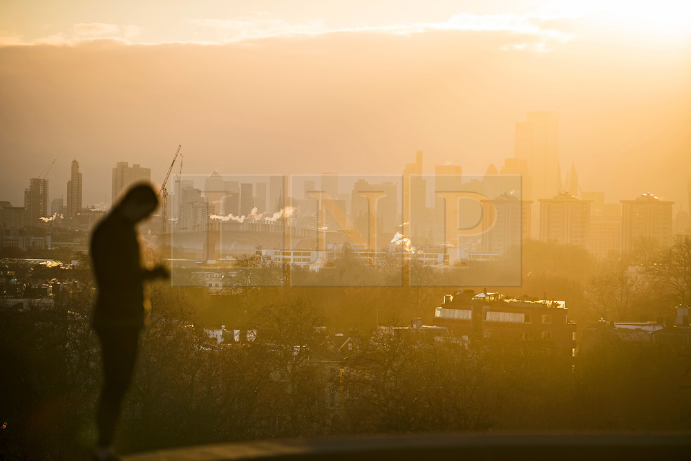 © Licensed to London News Pictures. 10/02/2021. London, UK. A woman watches as the sun rises over the city of London, as seen from Primrose Hill in Camden, north London, on another morning of sub zero temperatures in the capital. Photo credit: Ben Cawthra/LNP