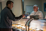 A prisoner collects his lunch from the wing canteen window. HMP/YOI Portland, Dorset. A resettlement prison with a capacity for 530 prisoners. Dorset, United Kingdom.