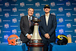 Florida Gators head coach Dan Mullen and Michigan Wolverines head coach Jim Harbaugh pose for a photo with the 2018 Chick-fil-A Peach Bowl trophy at the coaches news conference on Friday, December 28, 2018 in Atlanta. Florida and Michigan face off in the Peach Bowl NCAA football game on December 29, 2018. (Paul Abell via Abell Images for the Chick-fil-A Peach Bowl)
