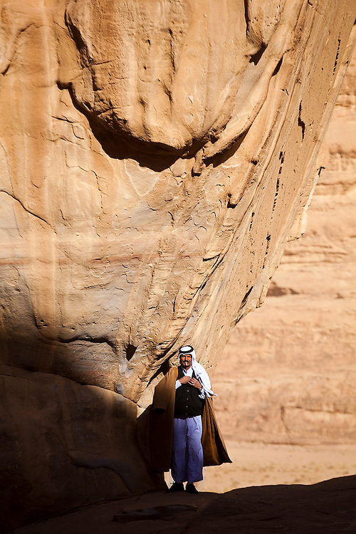 Zedane al-Zalabieh, owner of Bedouin Meditation Camp, stands smoking a cigarette at the base of Um Frouth Arch in Wadi Rum, Jordan.