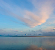 """Fog and pastel-colored clouds are reflected onto the water of Hornafjörður, a fjord in the Eastern Region of Iceland near Höfn. The Vatnajökull ice cap, the largest glacier in Europe, is visible on the horizon. Breiðabunga, a 3,468-foot (1,057-meter) ice-capped mountain, is among the peaks covered by the ice cap. Vatnajökull roughly translates to the """"water glacier."""""""