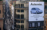 With a giant Volkswagen (VW) poster of their Lupo car in the foreground, we are viewing an aerial view of Via dei Condotti, the pedestrian street that runs west from the Spanish steps in the Italian capital, Rome. Written in the Italian language, the banner says the word Astemia which in English translates teetotaller, implying the vehicle is clean and non-polluting - in other words, zero emissions. This high viewpoint is taken from the top of the famous landmark where the height and perspective allows us to see down the street where shoppers to and fro amid the occasional vehicle crosses or is parked to make deliveries. On the corner of the poster building are balconies, terraces and the shuttered windows of apartments.
