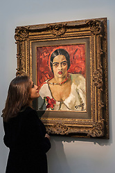 "© Licensed to London News Pictures. 02/10/2015. London, UK. A Sotheby's employee inspects ""Untitled"" by Amrita Sher-Gil (est. £1.5m - 2m), the highlight of the preview of Indian and Islamic Art Week at Sotheby's which runs from 2 to 7 October.  Photo credit : Stephen Chung/LNP"