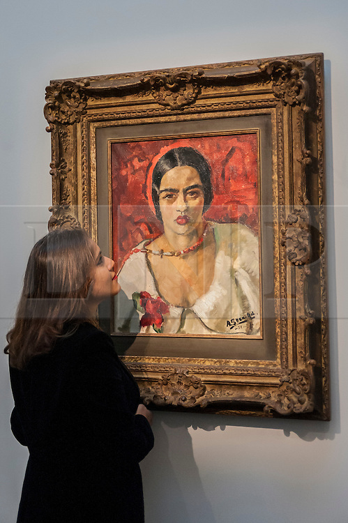 """© Licensed to London News Pictures. 02/10/2015. London, UK. A Sotheby's employee inspects """"Untitled"""" by Amrita Sher-Gil (est. £1.5m - 2m), the highlight of the preview of Indian and Islamic Art Week at Sotheby's which runs from 2 to 7 October.  Photo credit : Stephen Chung/LNP"""