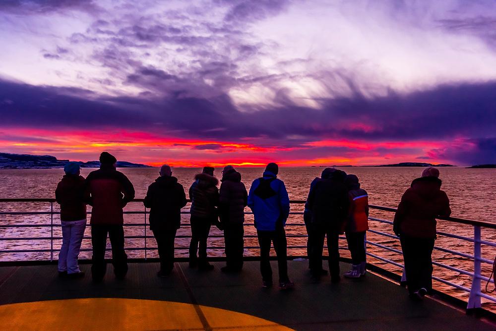Passengers aboard the Hurtigruten ship MS Vesteralen watch sunset in the winter near Roan, Norway.