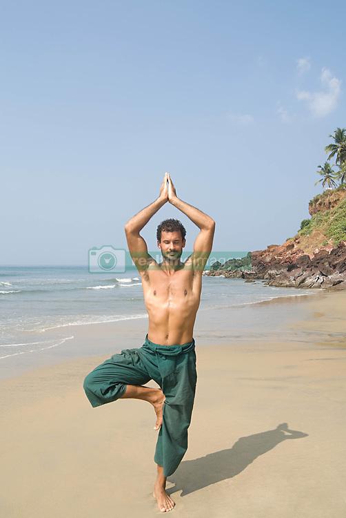 Jul. 26, 2012 - Man doing yoga on beach (Credit Image: © Image Source/ZUMAPRESS.com)