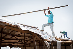 4 June 2019, Meiganga, Cameroon: CAR refugee Moussa Inoussa (centre) helps dismantle a building in the Ngam refugee camp. Deemed unsafe for use after days of strong wind, the building must be torn down and rebuilt in order to serve again as a distribution for food and other materials to the refugees. Supported by the Lutheran World Federation, the Ngam refugee camp, located in the Meiganga municipality, Adamaoua region of Cameroon, hosts 7,228 refugees from the Central African Republic, across 2,088 households.