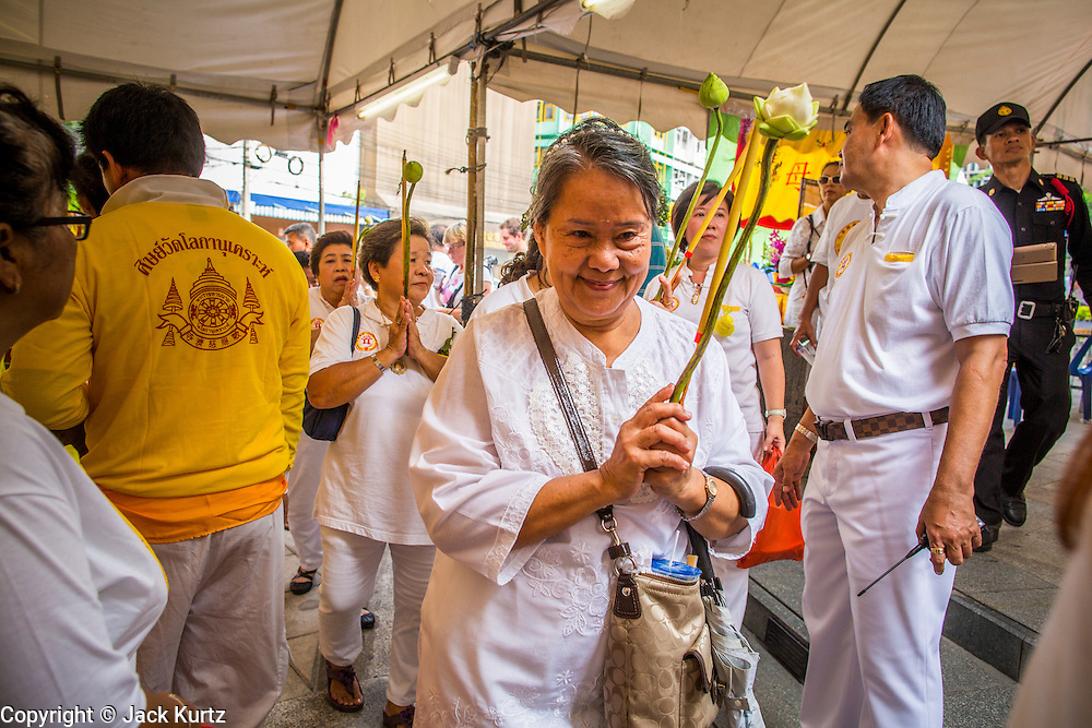 14 OCTOBER 2012 - BANGKOK, THAILAND:  Women in white, signifying that they have pledged to not eat meat for the Vegetarian Festival process into the merit making area in Chinatown in Bangkok on the first day of the Vegetarian Festival. The Vegetarian Festival is celebrated throughout Thailand. It is the Thai version of the The Nine Emperor Gods Festival, a nine-day Taoist celebration beginning on the eve of 9th lunar month of the Chinese calendar. During a period of nine days, those who are participating in the festival dress all in white and abstain from eating meat, poultry, seafood, and dairy products. Vendors and proprietors of restaurants indicate that vegetarian food is for sale by putting a yellow flag out with Thai characters for meatless written on it in red.     PHOTO BY JACK KURTZ