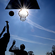 Kyrie Newall, 17, left, tosses the ball up for a layup as he's defended by Rico Newall, 16, both of Toledo, as they play basketball at Jamie Farr Park in Toledo on Tuesday, April 16, 2019. THE BLADE/KURT STEISS