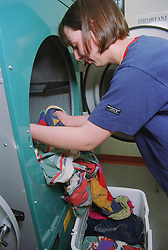 Female hostel resident putting clothes into drier in communal laundry room of 'shared living cluster',