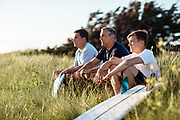 Father and sons sitting in the grassy sand dunes with their surfboards at St Ouen's Bay, Jersey watching the surf