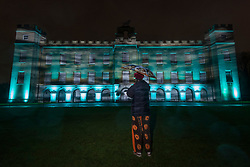© Licensed to London News Pictures. 15/11/2019. LONDON, UK. A visitor views a light projection as The Enchanted Woodland opens on a rainy evening at Syon House in West London.  An illuminated trail takes visitors through gardens designed by Capability Brown, round an ornamental lake and ends at the spectacular Great Conservatory.  The show is open to the public 15 November to 1 December.  Photo credit: Stephen Chung/LNP