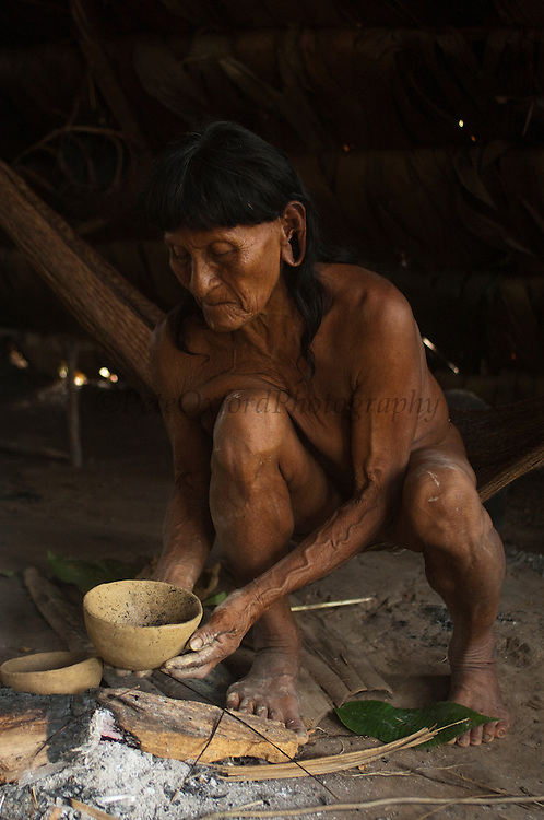 Huaorani Indian woman - Dabe Baiwa making a clay pot. Gabaro Community. Yasuni National Park.<br /> Amazon rainforest, ECUADOR.  South America<br /> The Huaorani clay pots have a unique shape compared with any of the other indian tribes in Ecuador.<br /> She has the typical stretched ear lobes common amoung the Huaorani. They often wear balsa ear plugs.<br /> This Indian tribe were basically uncontacted until 1956 when missionaries from the Summer Institute of Linguistics made contact with them. However there are still some groups from the tribe that remain uncontacted.  They are known as the Tagaeri. Traditionally these Indians were very hostile and killed many people who tried to enter into their territory. Their territory is in the Yasuni National Park which is now also being exploited for oil.