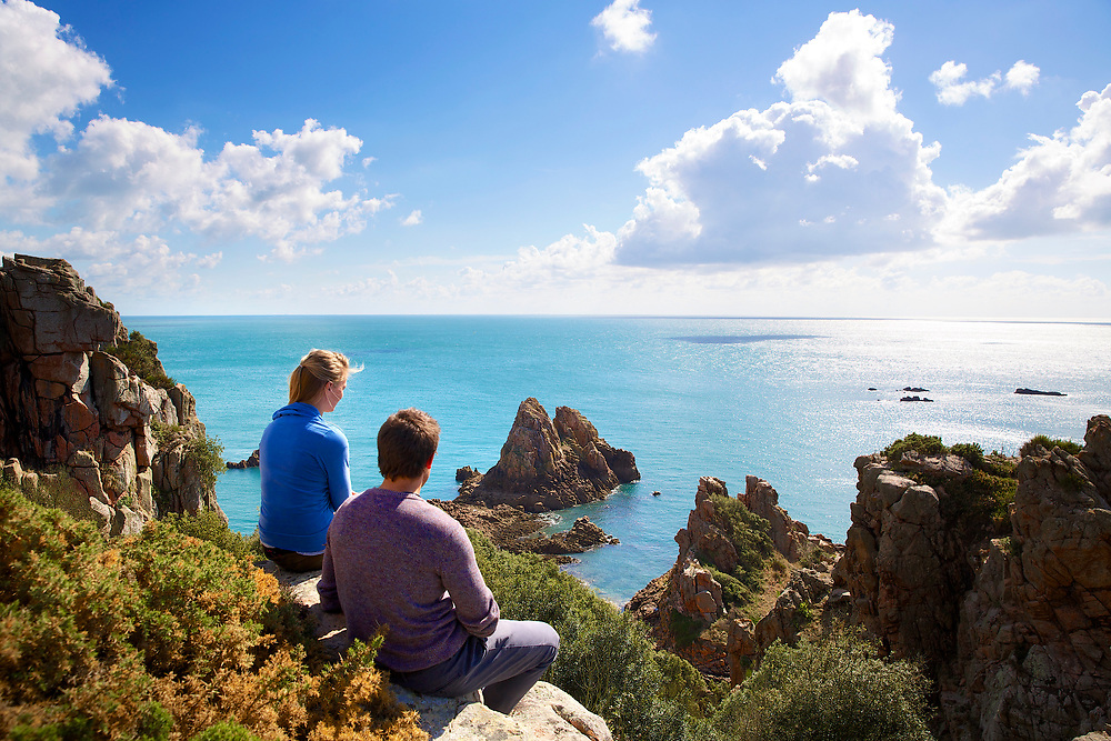 People sat on a cliff edge looking out over the rocks and cliffs around the South Coast and Beauport beach, Jersey, CI