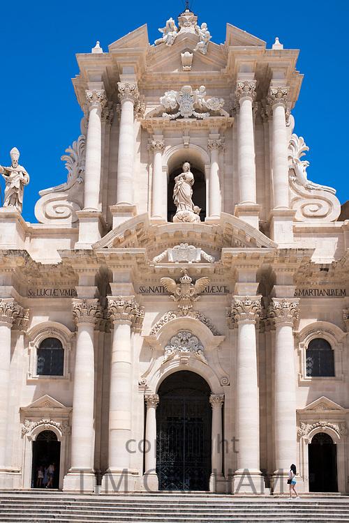 Tourist visitor at cathedral Duomo di Siracusa - Temple of Minerva - Tempio di Minerva - front elevation in Piazza Duomo, Ortigia, Sicily, Italy