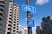 A cyle network route sign beneath new residential properties on the Silvertown Way regeneration development in Canning Town, Newham, on 11th August 2021, in London, England.