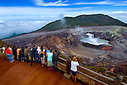 Tourists Admire The Green Steaming Sulphuric Crater Lake Of The Poas Volcano In Costa Rica.