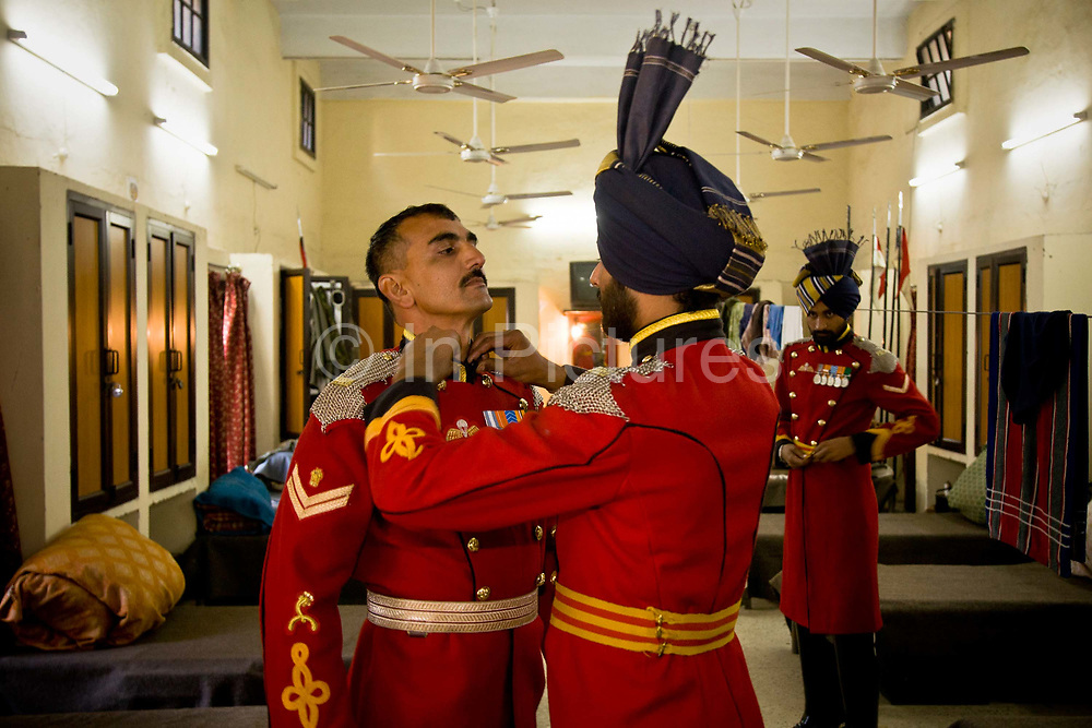 Presidential Bodyguard regiment (the PBG) soldiers get dressed into their ceremonial uniform as they prepare for the Changing of the Guard ceremony in front of the Presidential Palace, New Delhi, India. The PBG is the Indian Army's preeminent regiment founded in 1773 during the British occupation, this handpicked unit began with a mere 50 men and today stands at 160 soldiers plus 50 support staff. It has a dual role, both as a ceremonial guard for the President of India, with all its finery at important state functions, as well as an elite operational unit for the Indian Army which has seen action in many battle fronts, in particular the on going disputed region of Kashmir.