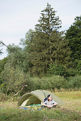 Teenage boy sitting near his camp tent in forest, Bavaria, Germany
