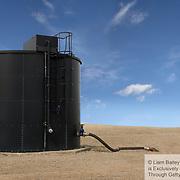 Single large oil tank. Blue sky, Oil pipe