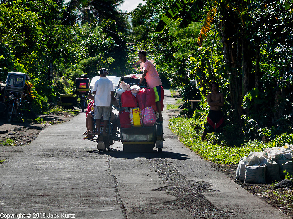 23 JANUARY 2018 - DARAGA, ALBAY, PHILIPPINES: People leave their community in Daraga Tuesday because of the eruption of Mayon volcano. The Mayon volcano continued to erupt Tuesday, although it was not as active as it was Monday. There were ash falls in communities near the volcano. This is the most active the volcano has been since 2009. Schools in the vicinity of the volcano have been closed and people living in areas affected by ash falls are encouraged to stay indoors, wear a mask and not participate in strenuous activities.    PHOTO BY JACK KURTZ