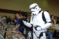 """A man dressed as a Stormtrooper from the movie """"Star Wars"""" looks through a selection of DVDs at the MegaCon comic books convention in Orlando, Florida."""